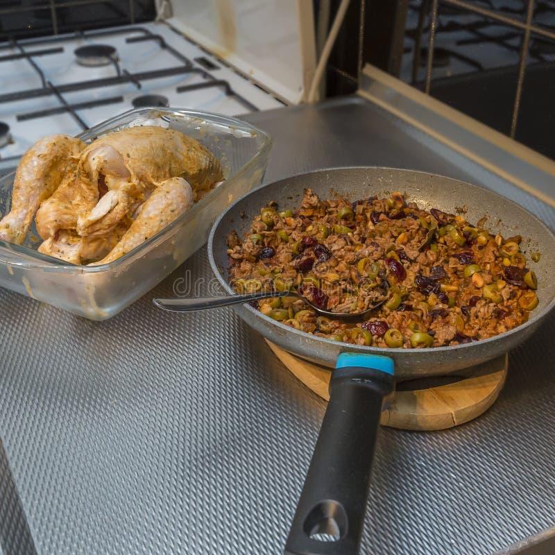 Bild av en ny och rå hel feg spridning med smör och bredvid en panna med jordnötkött som förbereds med oliv, russin, valnöt arkivfoton