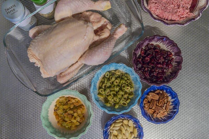 Bild av en rå hel höna och stoppaingredienser, jordningsnötkött, oliv, russin, tranbär, muttrar, mandlar och kryddor arkivbilder