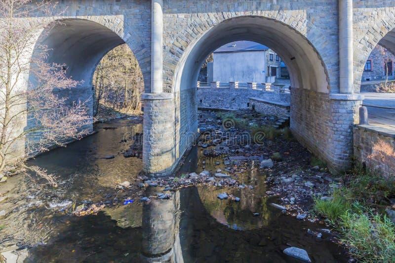 Bild av en stenbro med glest genomskinligt vatten royaltyfri foto