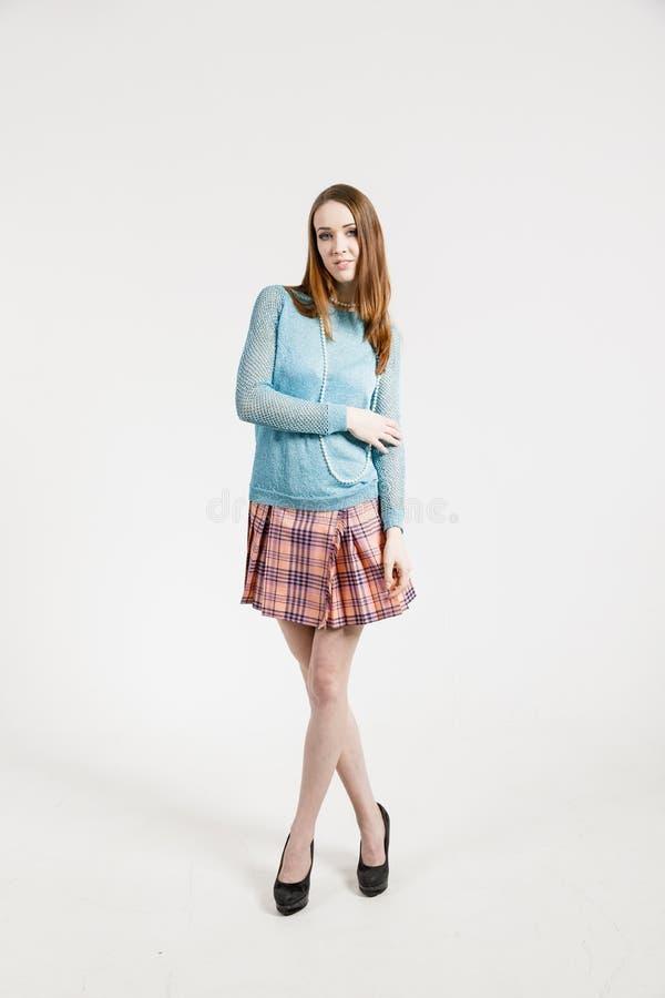 Bild av en ung kvinna som bär en kort kjol och en turkossweater arkivfoto