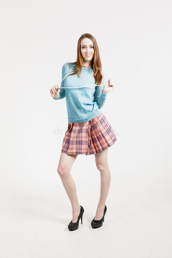Bild av en ung kvinna som bär en kort kjol och en turkossweater royaltyfri fotografi