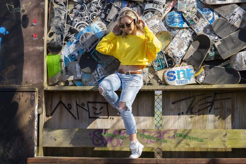 Bild av en ung kvinna som lyssnar och har gyckel, medan lyssna till musik till och med hörlurar, på en bakgrund av skateboarder arkivfoto