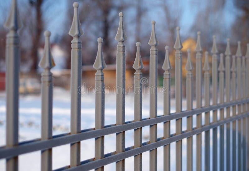 Bild av ett bearbetat staket för härligt dekorativt gjutjärn med det konstnärliga smidet Metallledstångslut upp arkivfoto