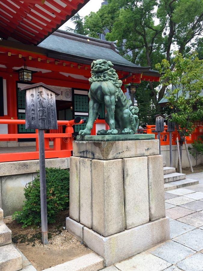 Bild av ett bronsKomainu hund-lejon som statyn av den Ikuta relikskrin i Kobe City, Japan royaltyfri fotografi