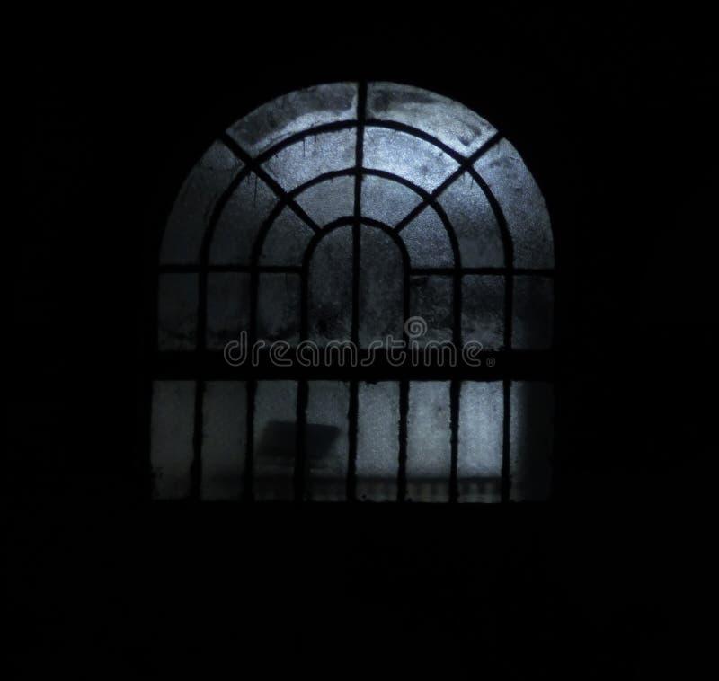 Bild av ett fönster på nattetid med några kusliga ljus arkivbilder