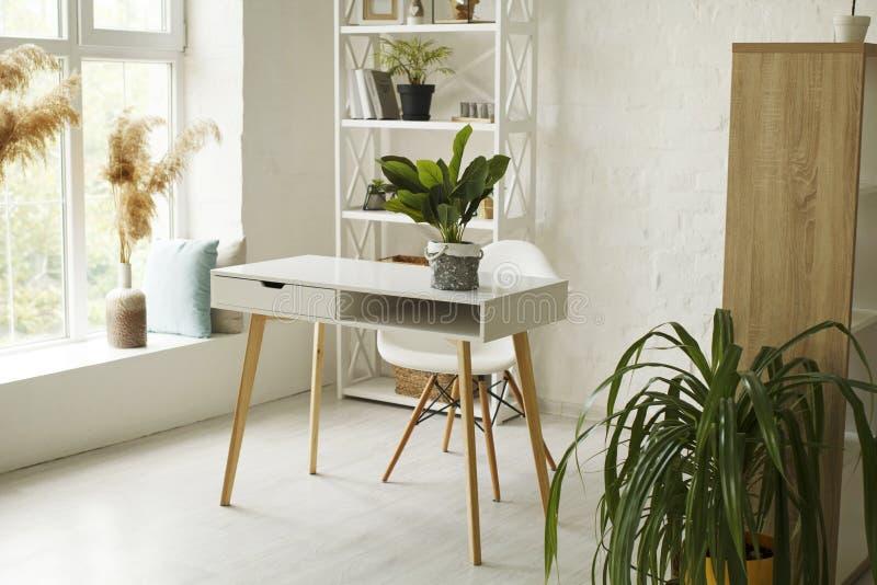 Bild av ett ljust vardagsrum med gröna växter och dekorationer arkivbilder