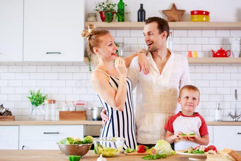 Bild av föräldrar och den unga sonen som förbereder mat i kök royaltyfri foto