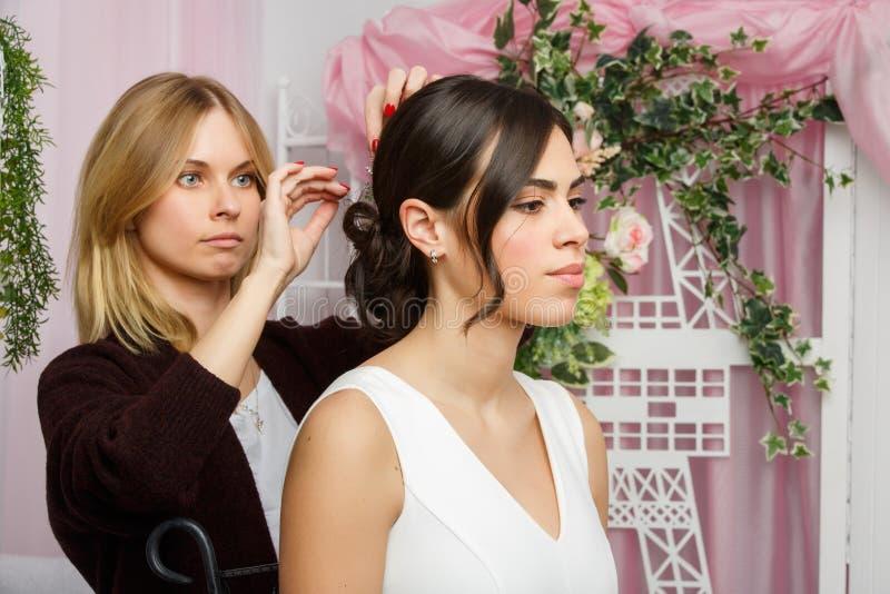 Bild av flickan och stylisten som justerar hår i rosa studio fotografering för bildbyråer