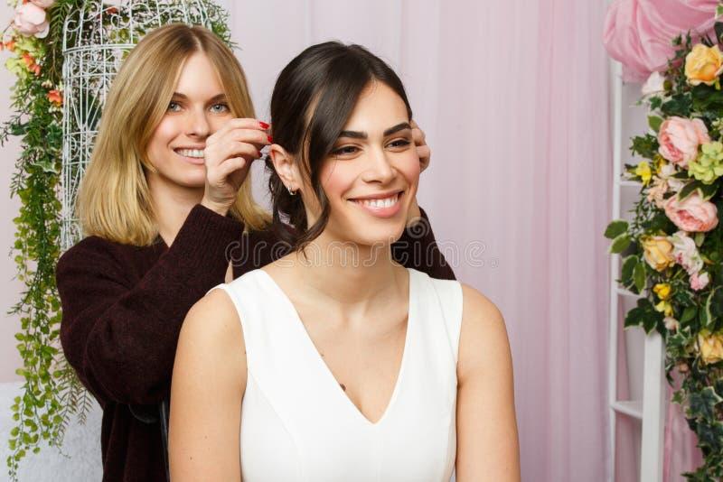 Bild av flickan och stylisten som justerar hår i rosa studio royaltyfri bild