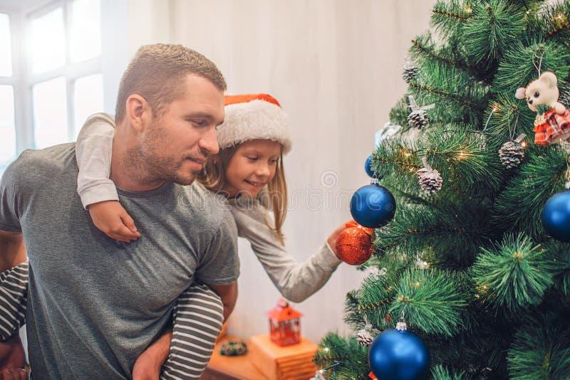 Bild av flickan som sitter på farsas baksida och dekorerar julgranen med leksaker Hon sätter där den röda leksaken Den unga manne royaltyfri foto
