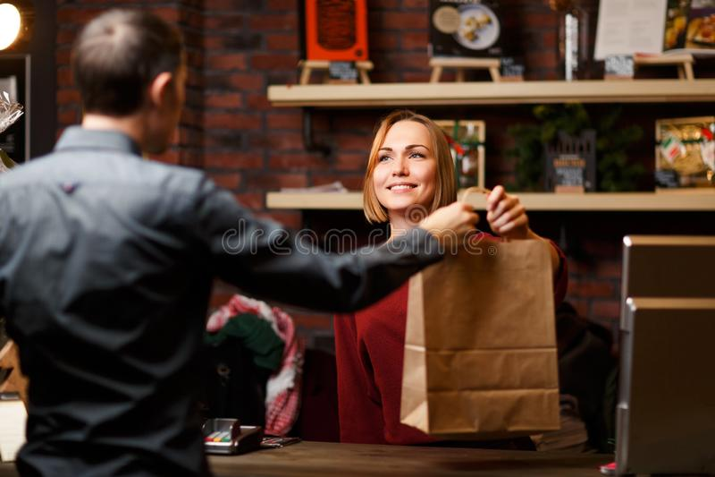Bild av flickasäljaren med papperspåsen och manshopparen från tillbaka arkivfoto