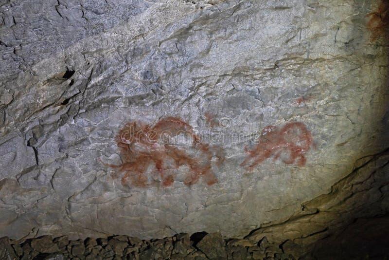 Bild av forntida djur på väggen av ockragrottan Historisk konst axeln royaltyfri foto