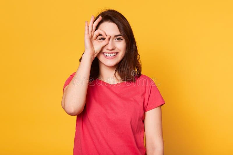 Bild av fridsamt gladlynt ungt posera för modell som isoleras över ljus gul bakgrund i studion som sätter hennes fingrar för att  arkivbild