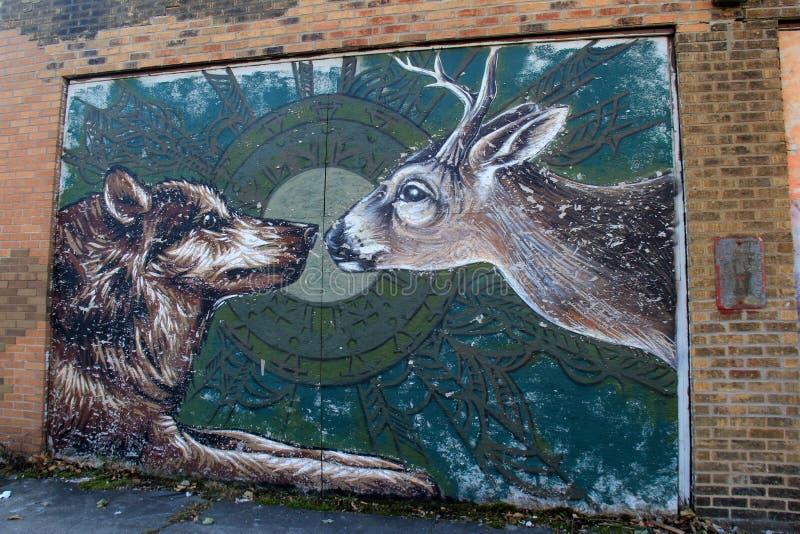 Bild av gatakonst, med vargen och hjortar som vänder mot av, Rochester, New York, 2017 royaltyfri foto