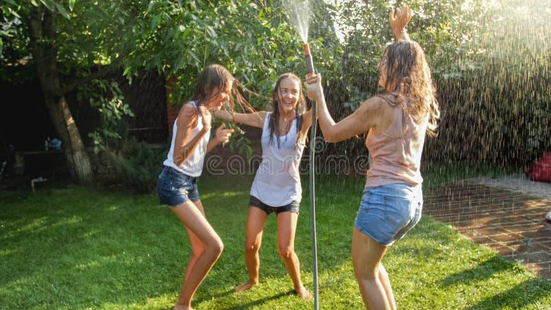 Bild av gladlynta skratta flickor i våt kläder som dansar i trädgården och rymmer vattenslangen Familj som spelar och har royaltyfri foto