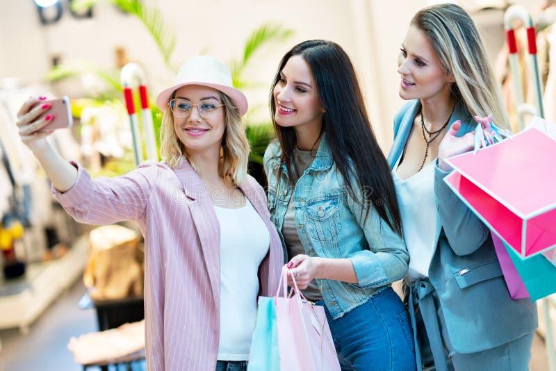 Bild av gruppen av lyckliga vänner som shoppar för kläder i galleria arkivbild