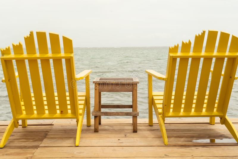 Bild av 2 gula adirondackstolar på en skeppsdocka royaltyfri foto