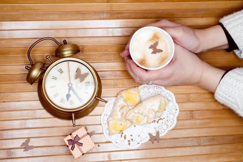 Bild av händer som rymmer koppen av den varma drinken med bakelser på plattan, den lilla gåvaasken och ringklockan omkring royaltyfri fotografi