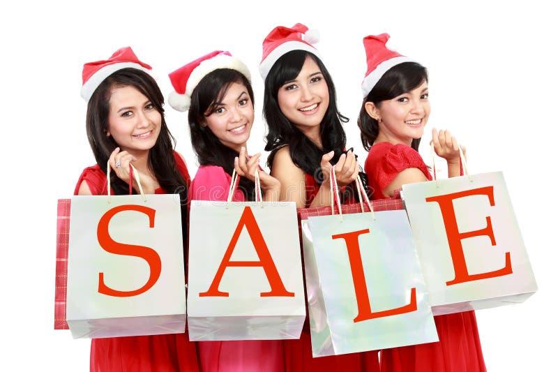 Bild av härliga fyra asiatiska kvinnor i röd klänning med shopping royaltyfria foton