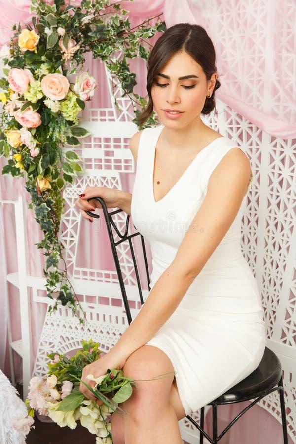 Bild av härligt brunettsammanträde på stol i den vita klänningen på bakgrund av blommor royaltyfri fotografi