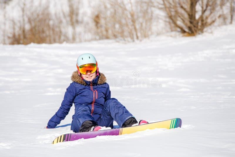 Bild av idrottsman nen i hjälm med snowboardsammanträde på den snöig kullen royaltyfri bild
