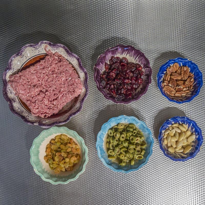 Bild av ingredienserna för förberedelsen av en fyllning med jordnötkött, oliv, russin, valnötter, mandlar och torkad blueberrie arkivbild