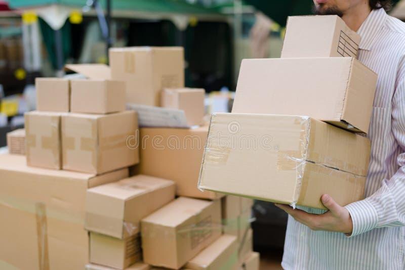 Bild av innehavet för stark man som flyttar 3 askar i lagerlagret, supermarket eller bakgrund för hylla för skärm för DIY-avdelni fotografering för bildbyråer