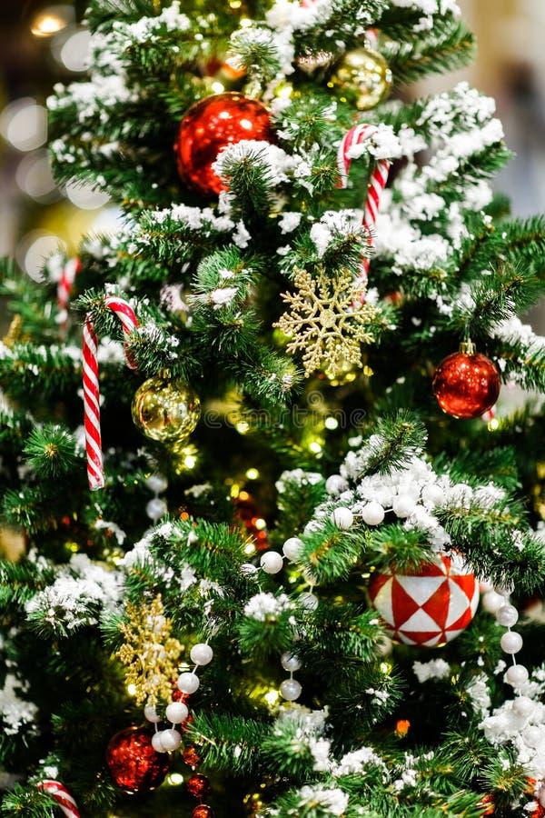Bild av julgranen med röda bollar, karamellrottingar, gåva, guld- snöflingor fotografering för bildbyråer