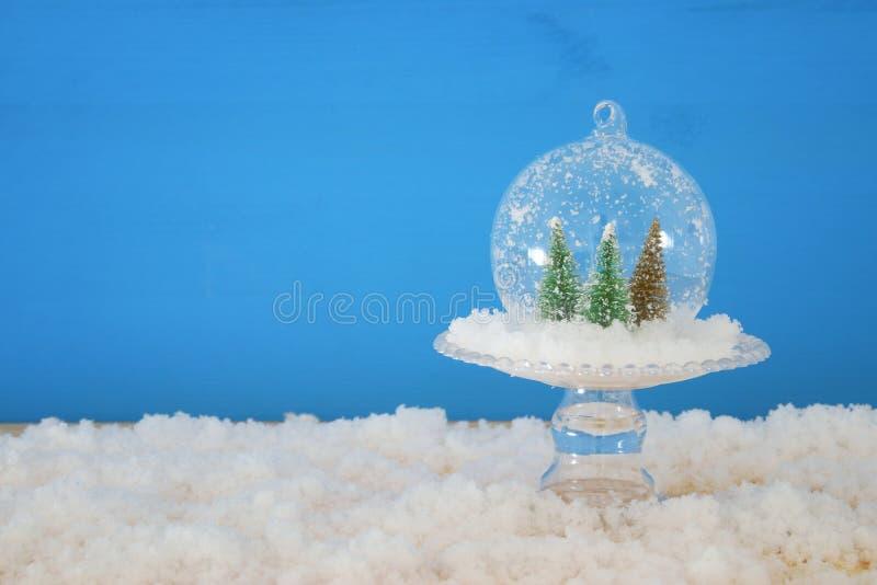 bild av julträd inom exponeringsglasboll över den snöig trätabellen royaltyfri foto