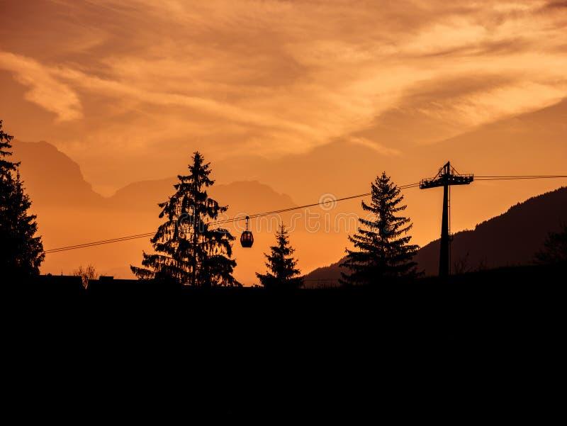 Bild av konturer av skidlift och träd under soluppgång i ottan arkivbilder