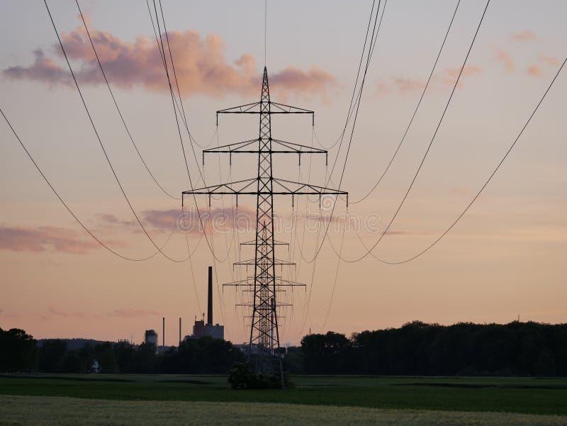 Bild av kraftledningen under solnedgång med kraftverket arkivbild