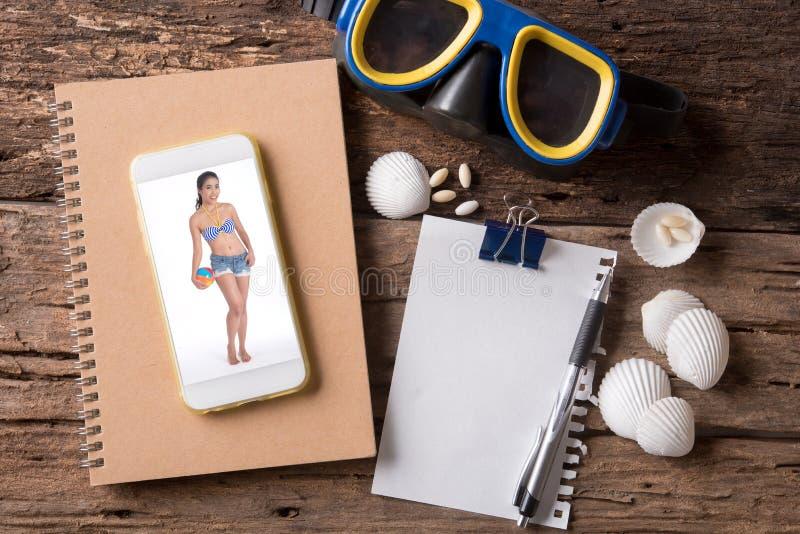 Bild av kvinnan i smart telefon och mellanrumsanmärkningsbok och skyddsglasögon arkivfoton