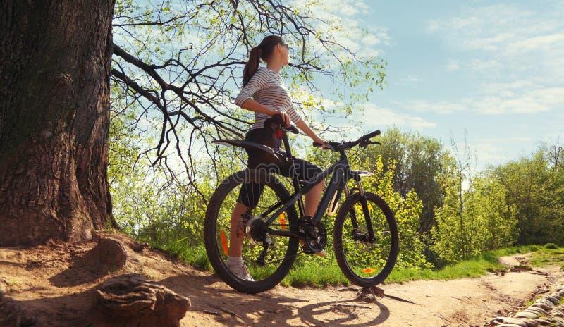 Bild av kvinnan med cykeln i en parkera arkivbild