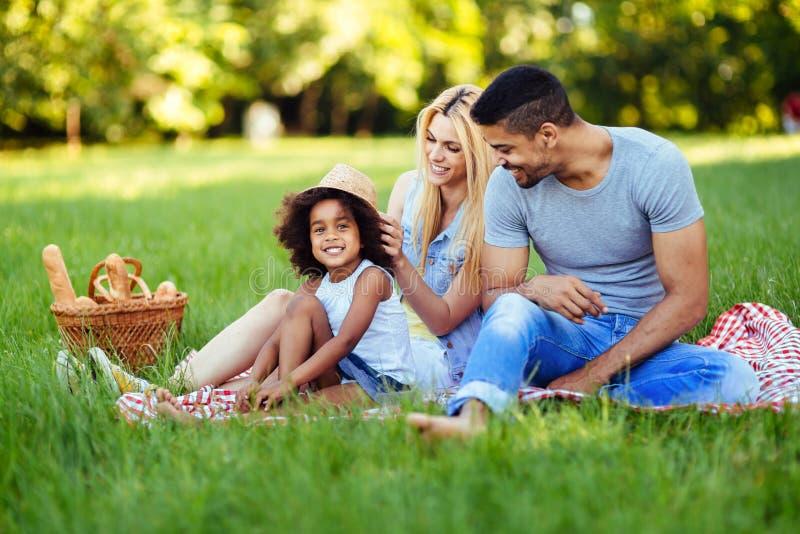 Bild av ?lskv?rda par med deras dotter som har picknicken arkivfoto