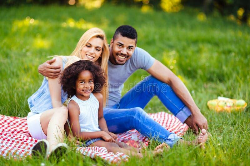 Bild av ?lskv?rda par med deras dotter som har picknicken royaltyfri foto
