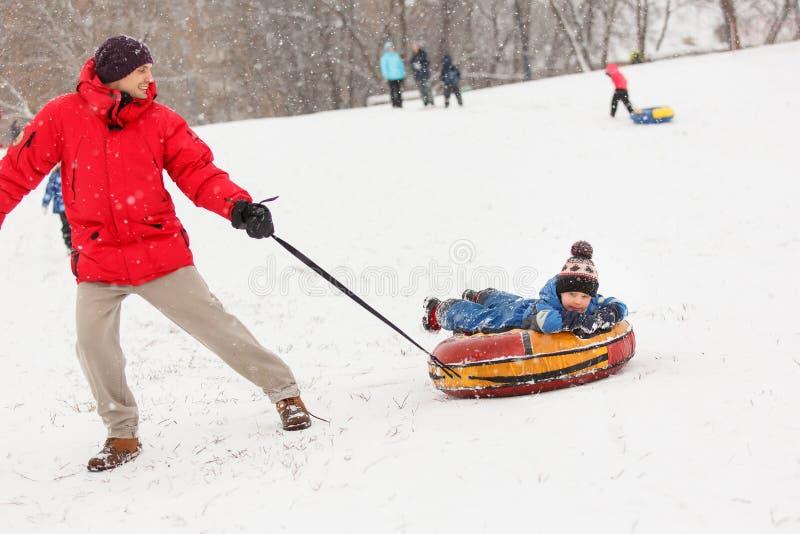 Bild av mannen som rullar hans son på vinterdag royaltyfri fotografi