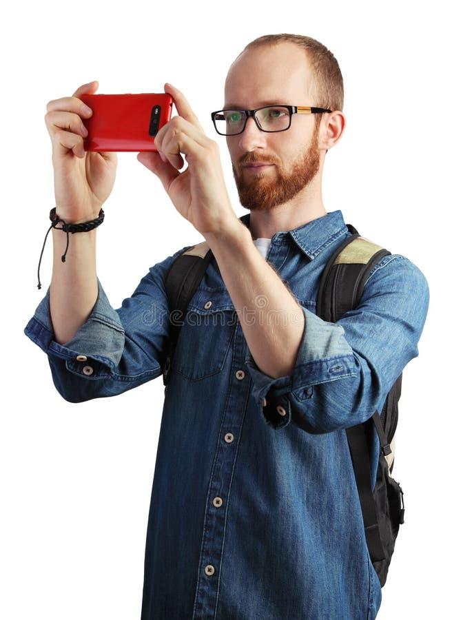 Bild av mannen som tar bilder med hans smartphone som isoleras på whi arkivfoton