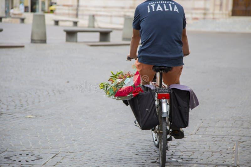 Bild av personen som cyklar med bagage i den historiska mitten royaltyfri fotografi