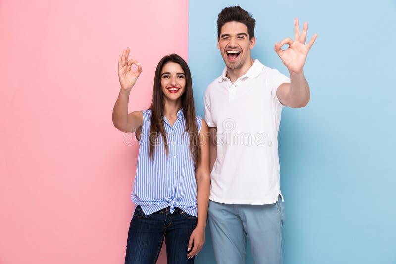 Bild av positiva par i tillfällig t-skjortor le och gesturin royaltyfri fotografi