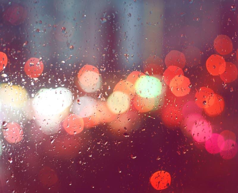 Bild av regndroppar på fönster på natten i staden arkivbild
