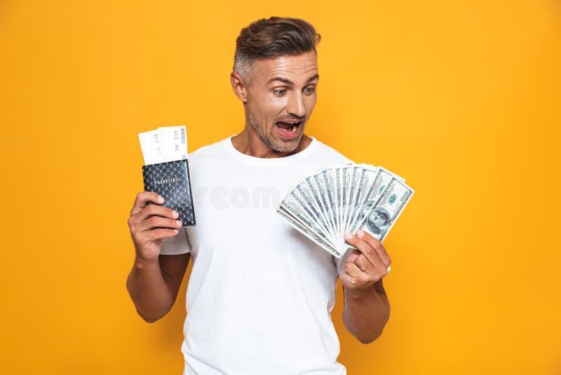 Bild av rikeman30-tal i den vita t-skjortan som rymmer pengarfan- och loppbiljetter royaltyfria foton