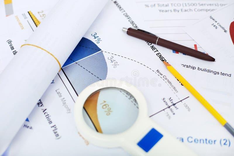 Bild av rullningspapper, pennan, blyertspennan och förstoringsglaset på det finansiella papperet arkivbild