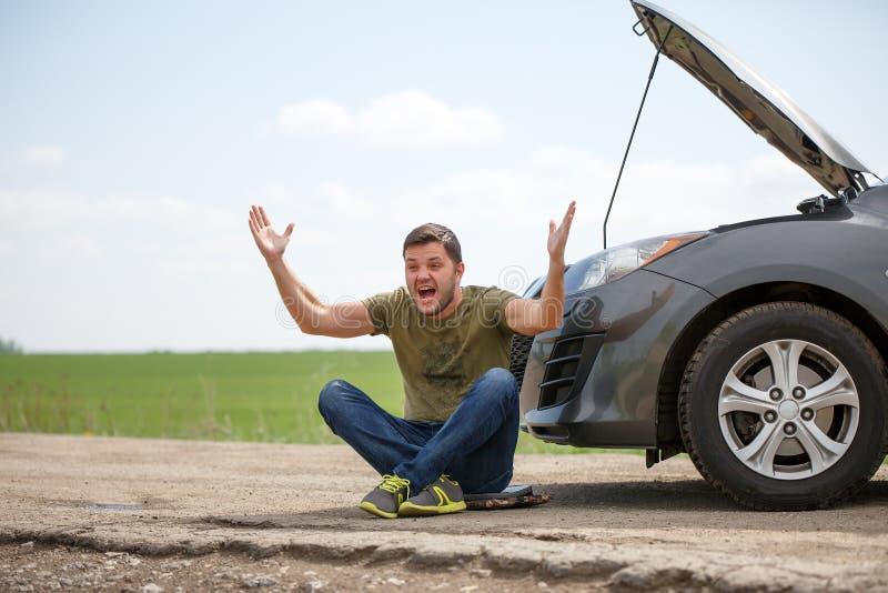 Bild av sammanträde för ung man bredvid den brutna bilen med den öppna huven arkivbild