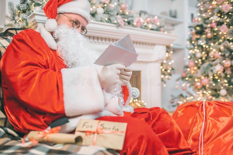 Bild av Santa Claus som sitter och läser brev Han rymmer dem i händer Mannen är koncentrerad och allvarlig royaltyfria bilder