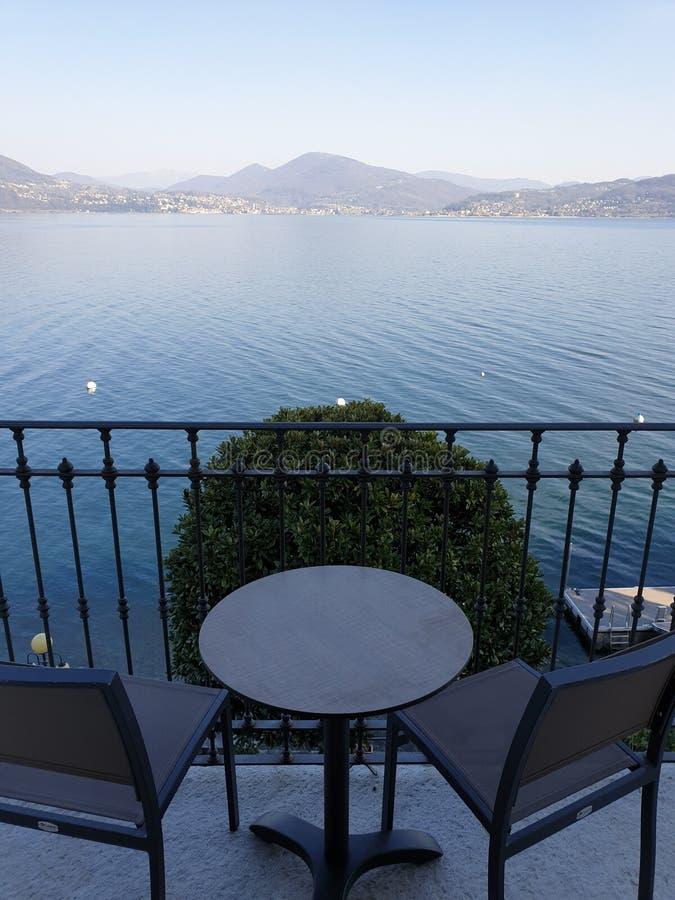 Bild av sikten från balacony med stolar och tabellen på en härlig sjö med mountins i bakgrunden royaltyfri bild