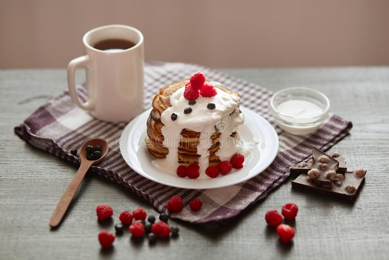 Bild av smakliga pannkakor med blåbär och hallon på den vita plattan, på den mörka bruna bakgrunden, kopp te eller coffe för färg arkivbild