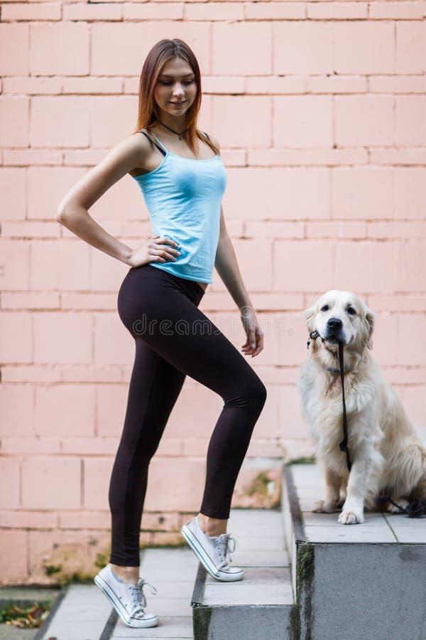 Bild av sportbrunetten med labrador nära byggnadsväggen royaltyfri bild