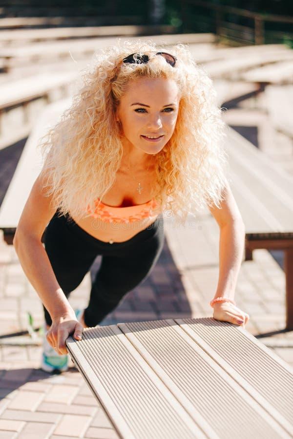 Bild av sportkvinnan som övar bland bänkar i sommardag royaltyfri fotografi