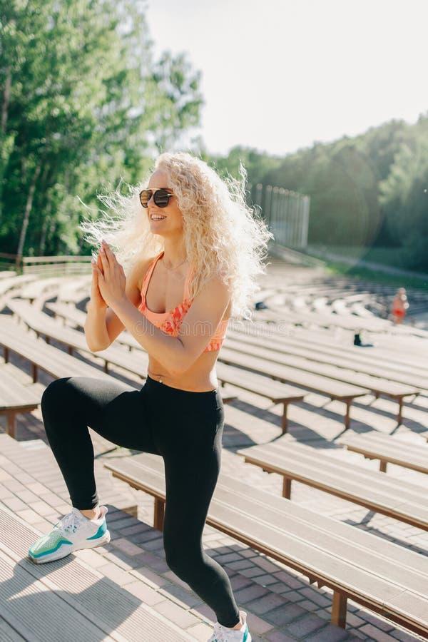 Bild av sportkvinnan som övar bland bänkar i sommardag royaltyfria foton
