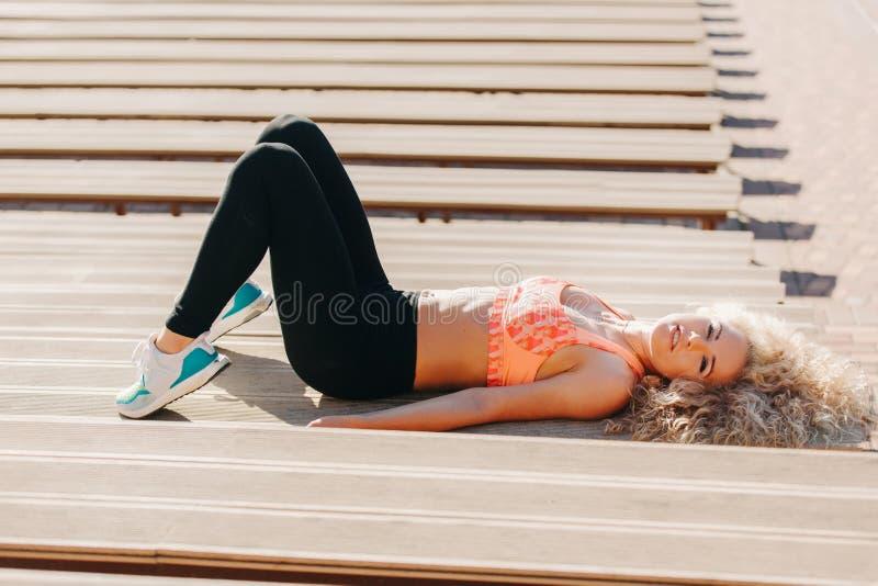 Bild av sportkvinnan som övar bland bänkar i sommardag fotografering för bildbyråer